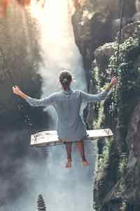 Woman swinging over a cliff